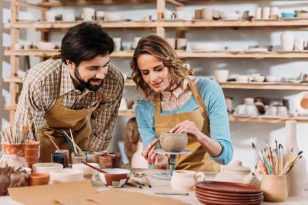 Photo pour Couple de potiers décorant bol en céramique dans l'atelier - image libre de droit