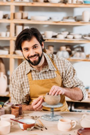 Photo for Smiling potter in apron looking at camera and decorating ceramics in workshop - Royalty Free Image
