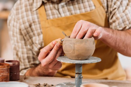 cropped view of potter making ceramic bowl in workshop