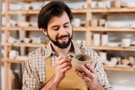 bearded man in apron decorating ceramics in pottery workshop