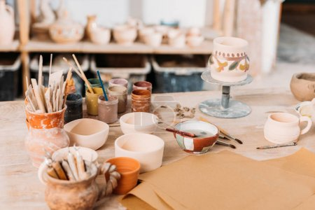 ceramics and paints on wooden table in pottery workshop