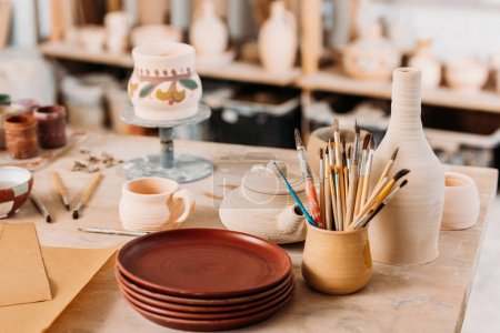 ceramic dishware and brushes on wooden table in pottery workshop