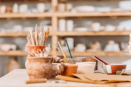 selective focus of ceramics and pottery tools on wooden table in workshop