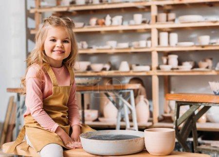 Rubio niño sonriente en la clase de cerámica