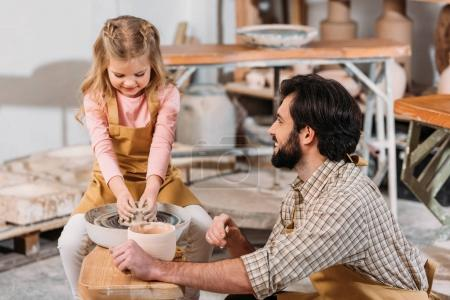 adorable kid making ceramic pot on pottery wheel with teacher