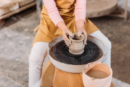 cropped view of kid making ceramic pot on pottery wheel in workshop