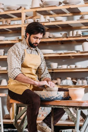 potter making ceramic pot on pottery wheel in workshop
