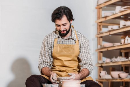 man in apron making ceramic pot on pottery wheel in pottery workshop