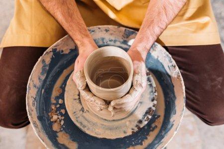 Photo pour Vue du dessus des mains avec pot en céramique sur roue de poterie en atelier - image libre de droit