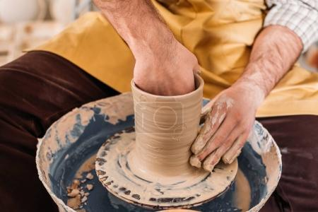 cropped view of potter making ceramic pot on pottery wheel