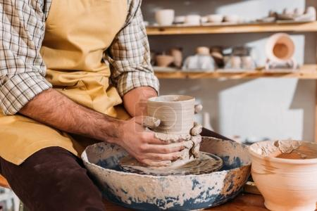 partial view of male hands with ceramic pot on pottery wheel