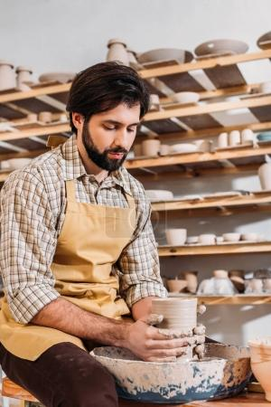 bearded potter making ceramic dishware on pottery wheel in workshop