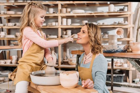 adorable happy daughter touching nose of mother in pottery workshop