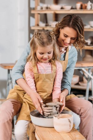 teacher and kid making ceramic pot together on pottery wheel