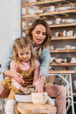mother and daughter making ceramic pot on pottery wheel together
