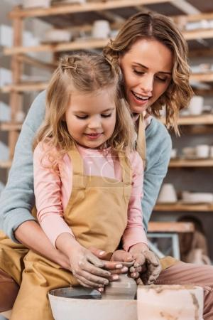 happy mother and daughter making ceramic pot in pottery workshop