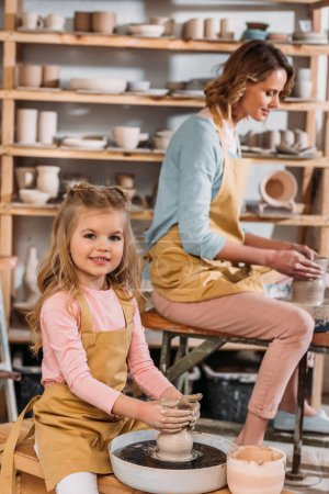 teacher and kid making ceramic pots on pottery wheels in workshop