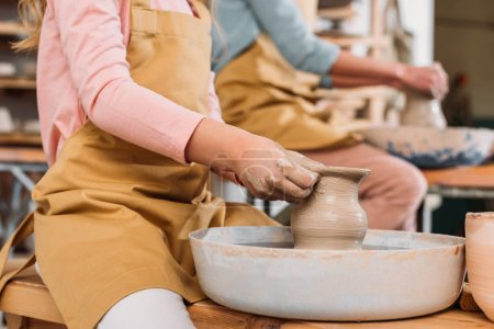 cropped view of teacher and child making ceramic pots on pottery wheels