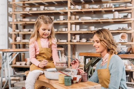 female teacher and child painting ceramic pot in pottery workshop with shelves