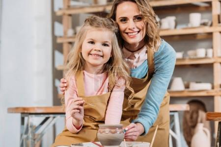 smiling teacher and child painting ceramic pot together in pottery workshop