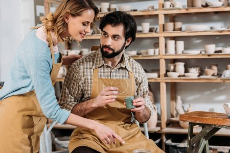 female potter teaching bearded man how to paint ceramics in workshop