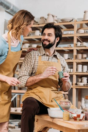female potter teaching man how to paint ceramics in workshop