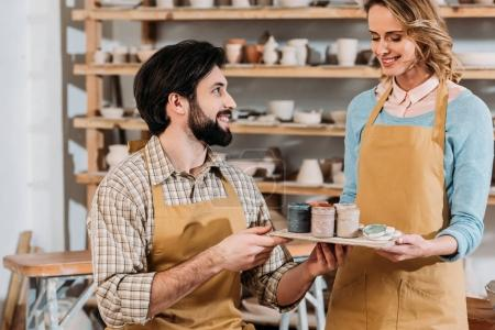 smiling couple in aprons with paints in pottery workshop