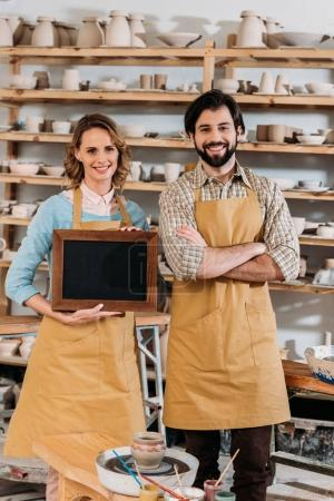 two owners holding chalkboard in pottery workshop with ceramics on shelves