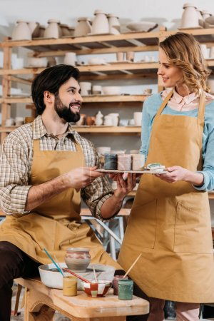 couple in aprons with paints in pottery workshop