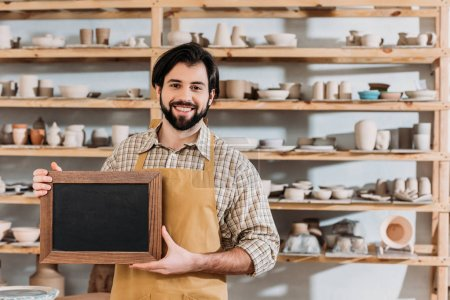 Photo for Male bearded owner with chalkboard in pottery workshop with ceramics - Royalty Free Image