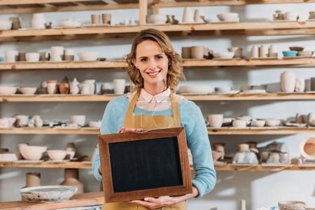 Photo for Beautiful smiling owner with chalkboard in pottery workshop - Royalty Free Image