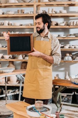 smiling male owner holding chalkboard in pottery workshop