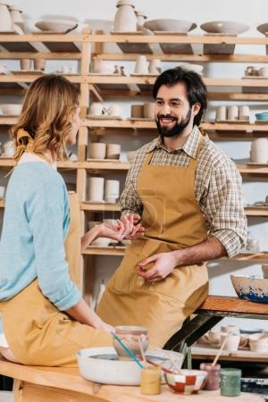 happy couple in aprons with ceramics and paints in pottery workshop