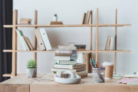 headphones, books and coffee on table in light interior