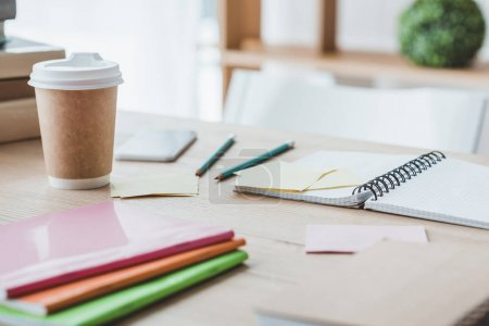 close up of educational copybooks and disposable cup of coffee on table