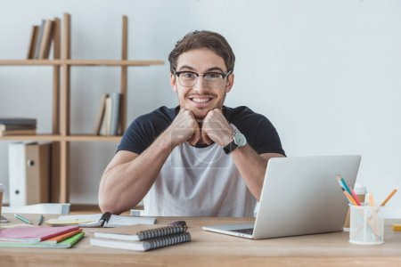 Photo pour Étudiant joyeux assis à la table avec des cahiers et ordinateur portable - image libre de droit