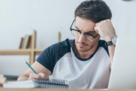 Photo pour Beau mâle étudiant en lunettes de vue par écrit dans le cahier - image libre de droit