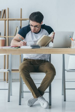 handsome male student in glasses studying with book and laptop