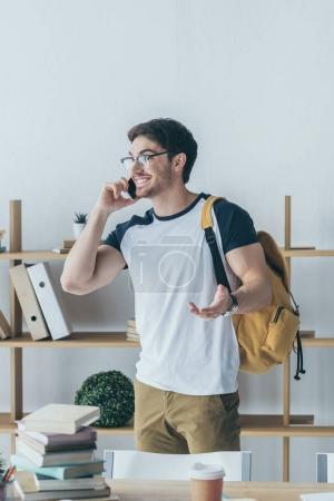 Photo pour Élève de sexe masculin heureux avec sac à dos parler sur smartphone - image libre de droit