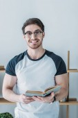 cheerful handsome student holding book