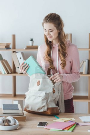 attractive smiling girl putting book into backpack