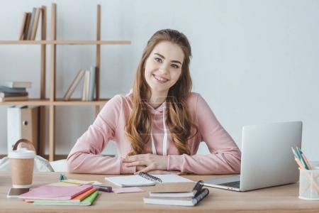 Photo pour Étudiante souriante assise à table avec ordinateur portable et copybooks - image libre de droit