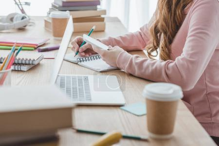 Photo for Cropped view of female student studying with digital devices and books - Royalty Free Image