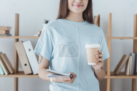 cropped view of girl holding copybook and coffee to go