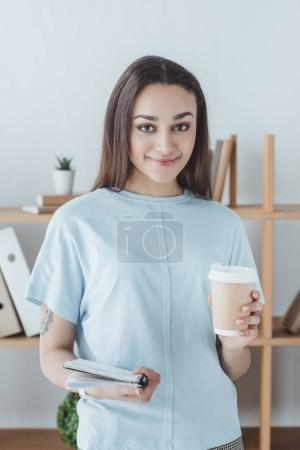 beautiful smiling girl holding copybook and cup of coffee