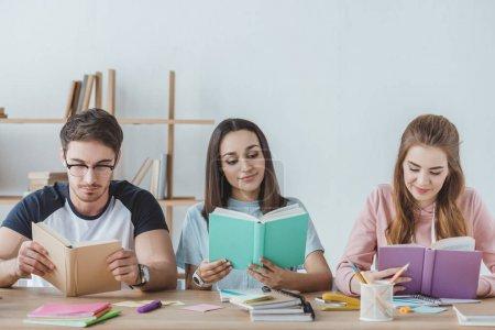 Photo pour Jeunes étudiants multiethniques lisant des livres - image libre de droit