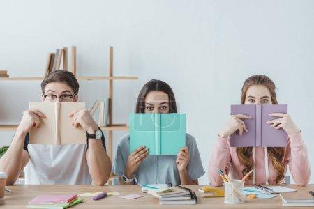 Photo pour Trois jeunes étudiants tenant des livres assis à table - image libre de droit