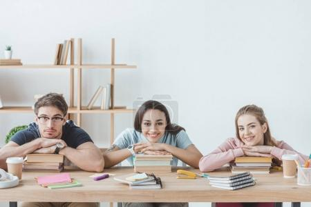 young multicultural students sitting at table with books and copybooks