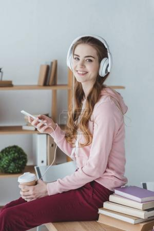 smiling blonde student with coffee listening music with smartphone and headphones
