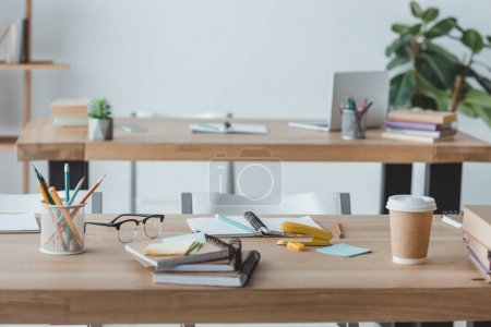 classroom interior with copybooks and cup of coffee on tables